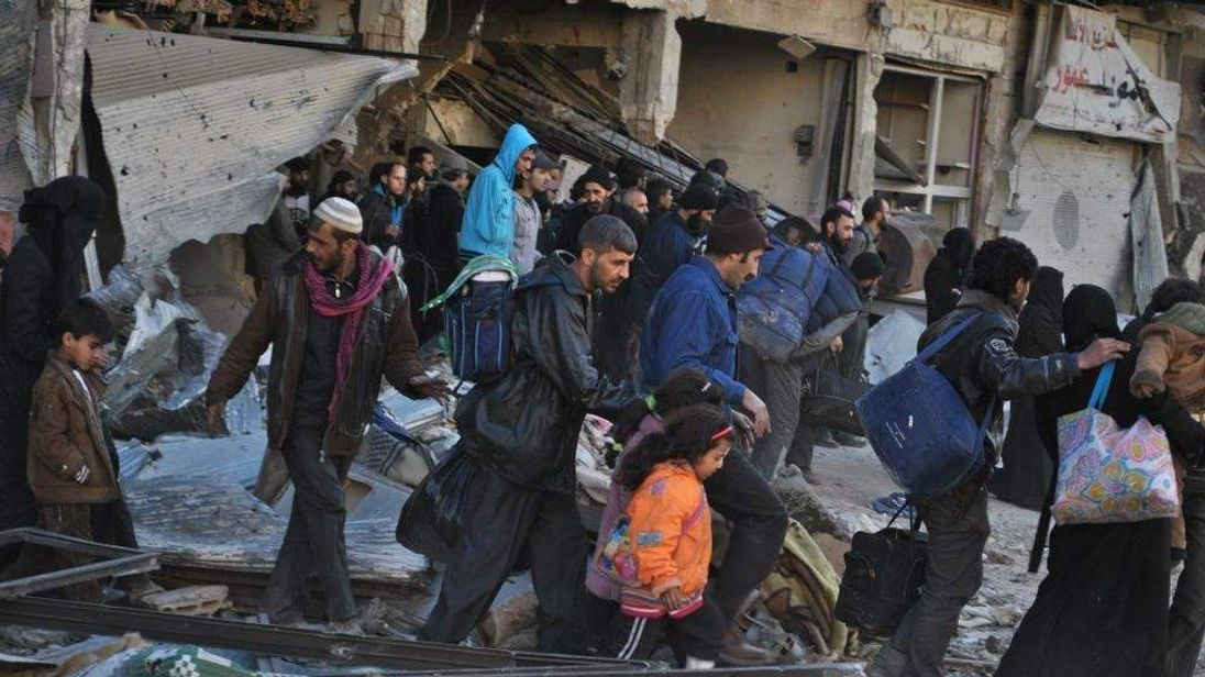 Syrian civilians walk as they are evacuated during a humanitarian operation in the besieged Syrian city of Homs