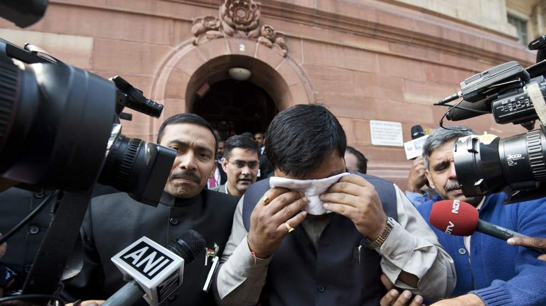 Indian politician dabs his eyes after pepper spray was fired in parliament