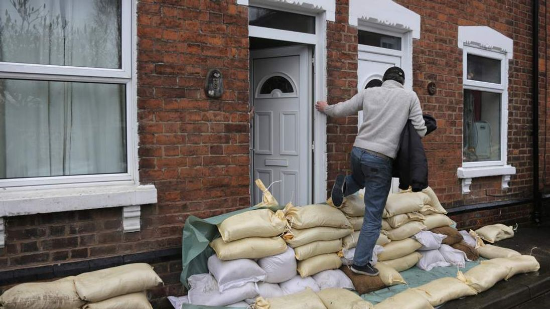 A man steps over sandbags in front of a property in Alney Island, Gloucester