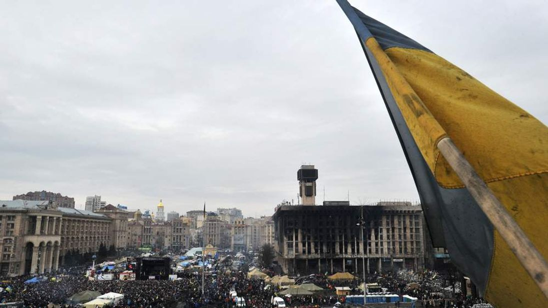 A Ukrainian flag flies over Independence Square in central Kiev as people visit memorials to anti-government protesters killed in clashes with police.