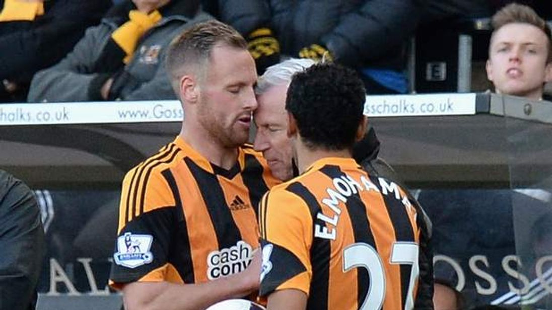 David Meyler of Hull City clashes with Alan Pardew, Manager of Newcastle United.