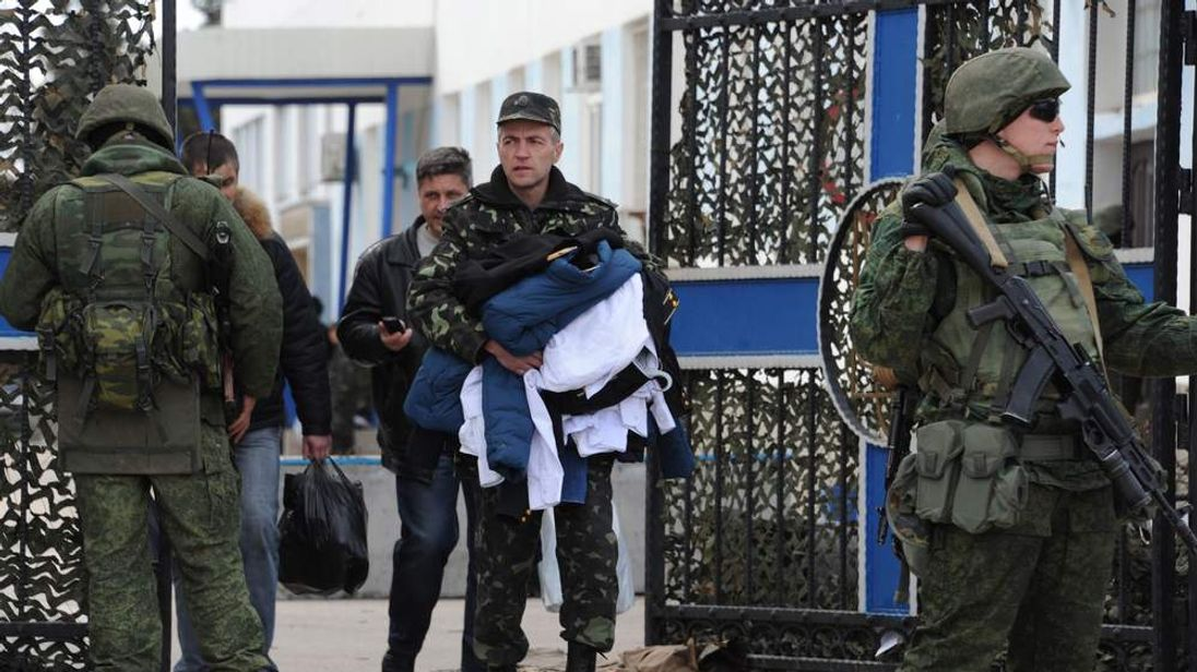 Ukrainian soldiers leave a navy base in Sevastopol as Russians stand guard.