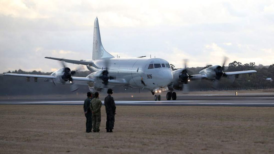 Ground crew look on as a South Korean Navy P-3C Orion taxis after returning from searching for Malaysian Airlines Flight MH370.