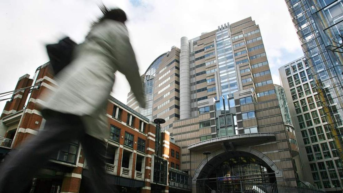 A City worker passes the headquarters of bank JP Morgan Chase in London
