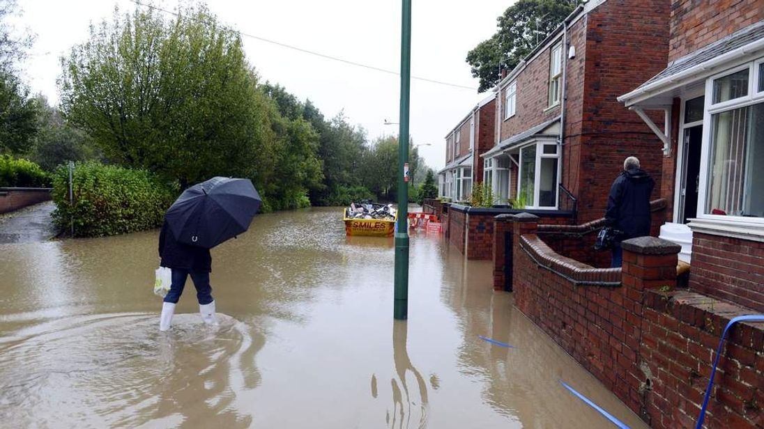 Residents make their way through flood water in Chester-Le-Street, as persistent heavy downpours continued, causing some areas to experience a whole month's rainfall in just 24 hours.