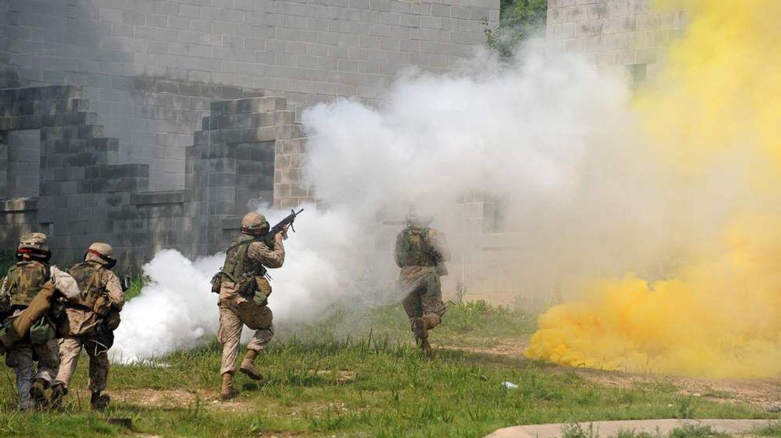 US Marines use smoke grenade as they att