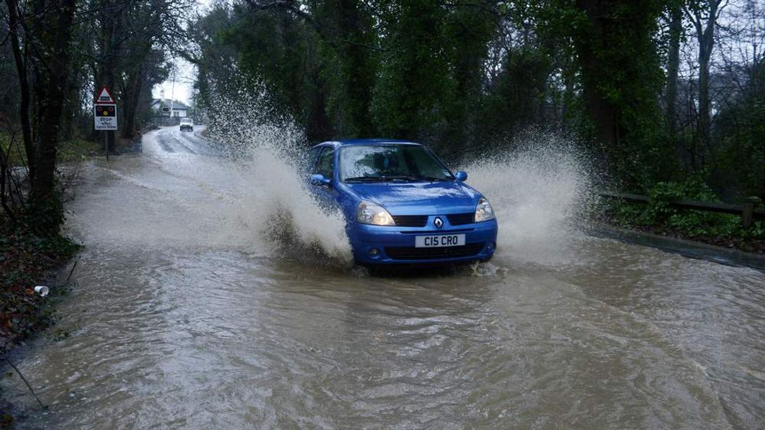 A car makes its way along a flooded road in Seaham