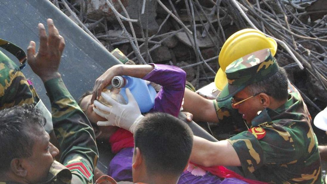 Rescuers carry a survivor pulled out from the rubble of a building that collapsed in Saver, near Dhaka, Bangladesh