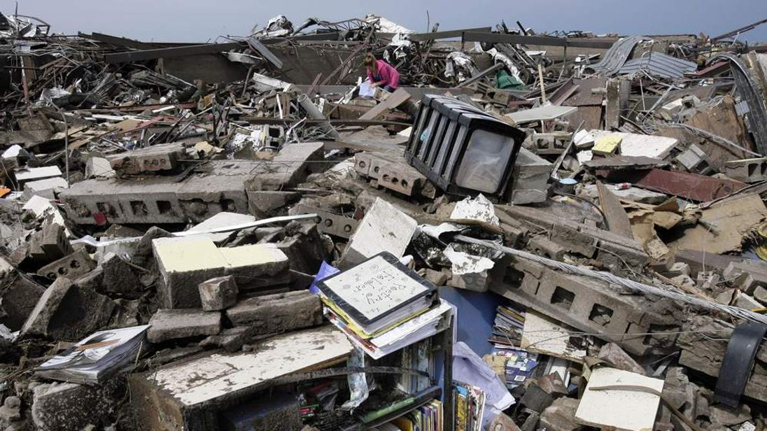 A teaching assistant sifts through the rubble at Briarwood Elementary School in Moore.