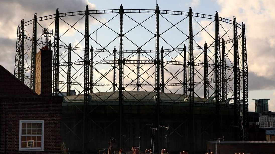 A gasometer stands half-full of natural gas