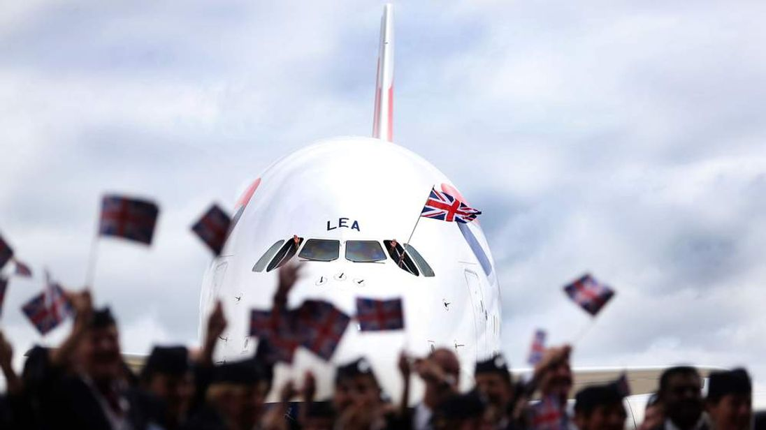 British Airways staff wave flags in front of a Airbus A380.