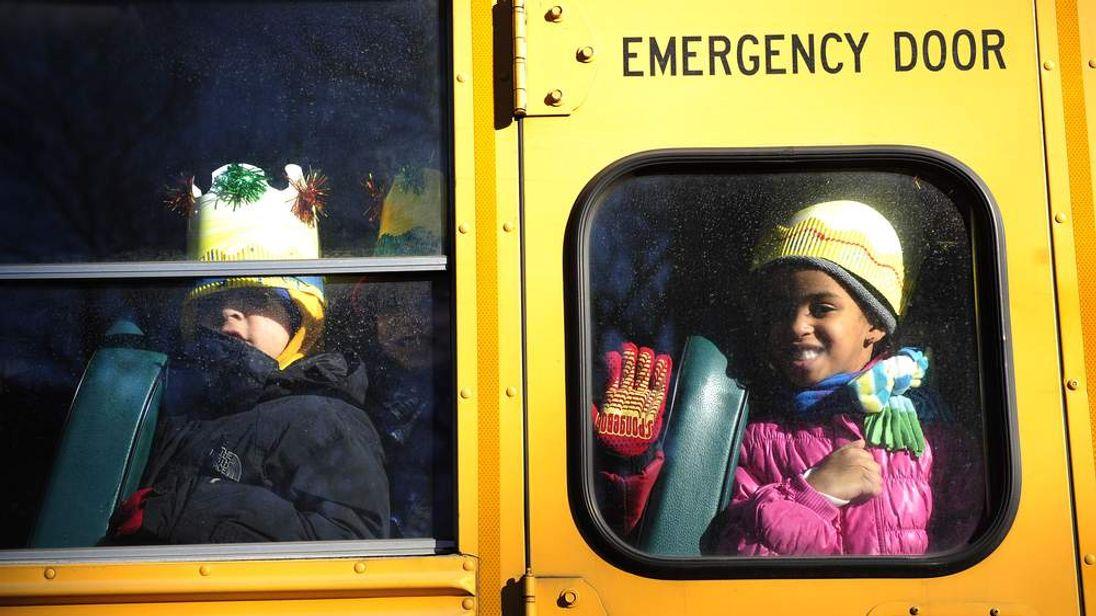 Children await to unload from a school b