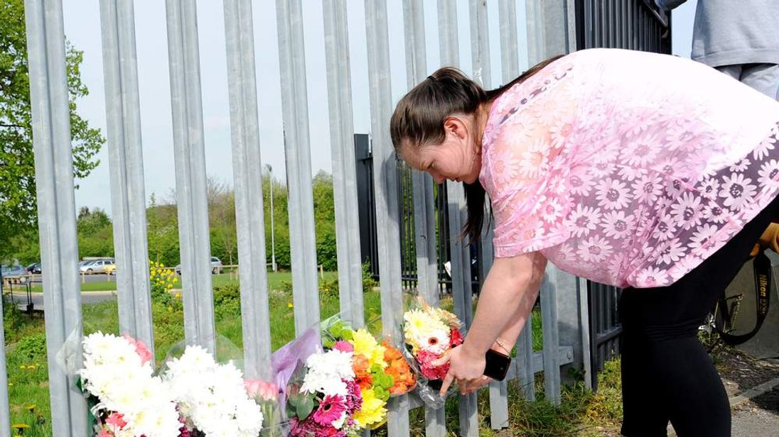 A woman lays flowers outside Corpus Christi Catholic College