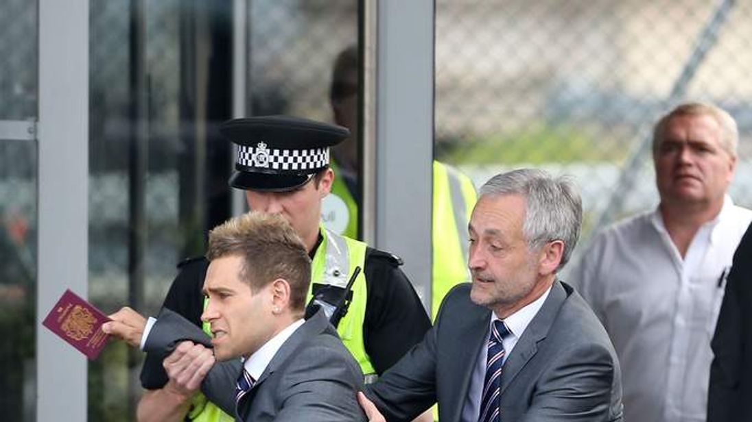 Comedian Simon Brodkin is taken away by security at Luton Airport.