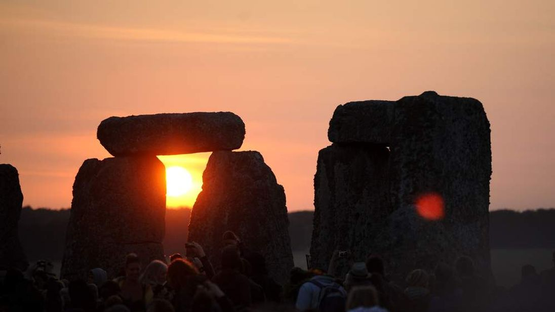 The sun rises above the horizon as dawn breaks behind the stones at Stonehenge in Wiltshire during the Summer Solstice.