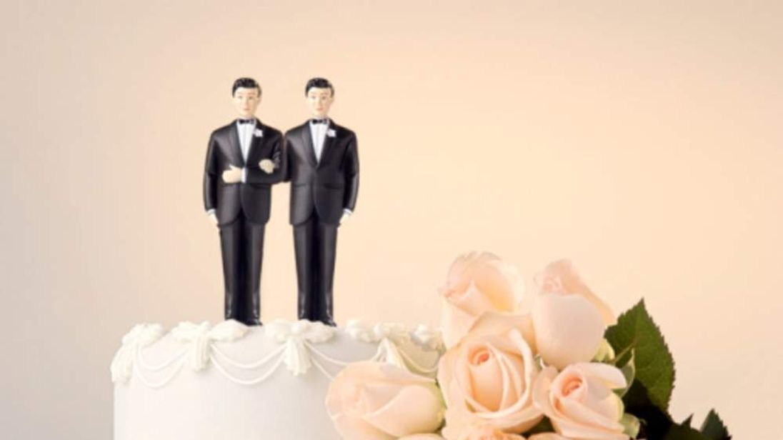 Two Groom Models On Top Of Wedding Cake