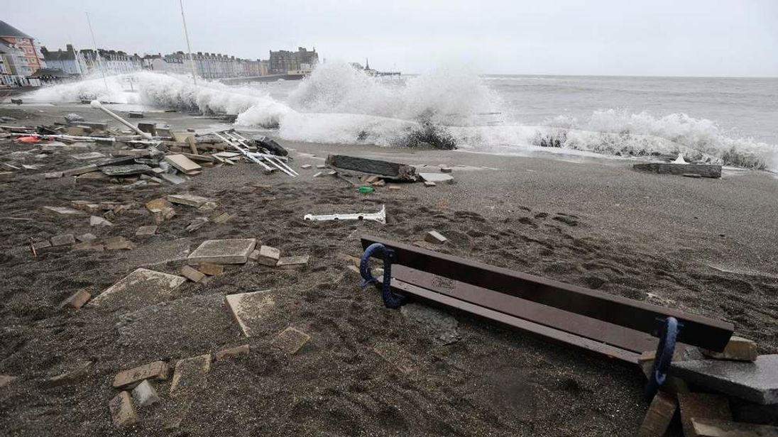 A large wave crashes over promenade at high tide in Aberystwyth