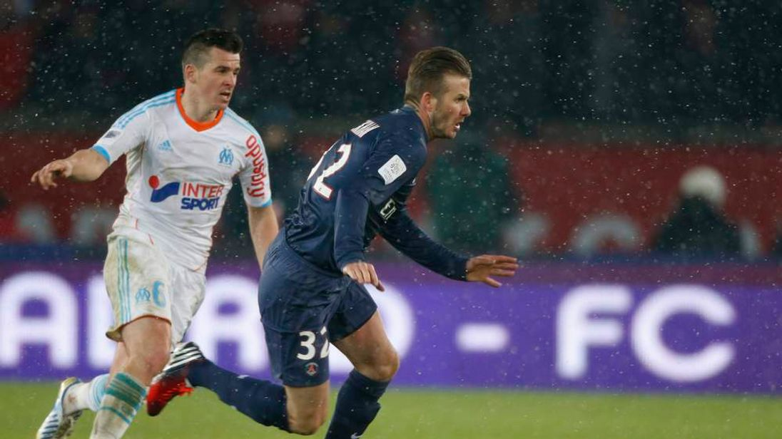 Paris Saint-Germain's Beckham challenges Olympic Marseille's Barton during their French Ligue 1 soccer match at Parc des Princes stadium in Paris