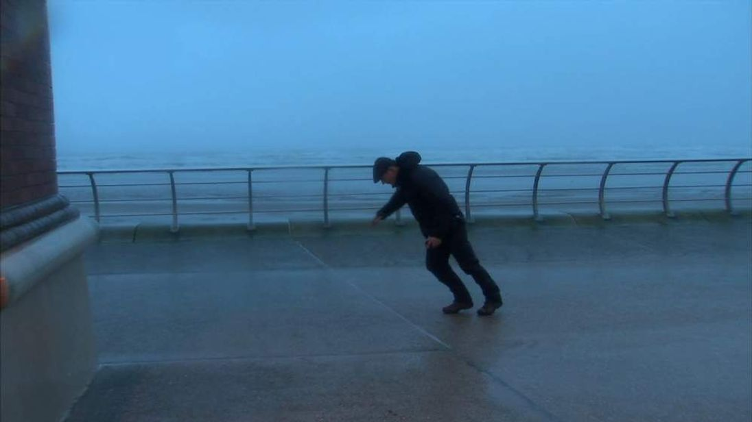 Sky's Andrew Wilson struggles to walk in the high winds in Blackpool
