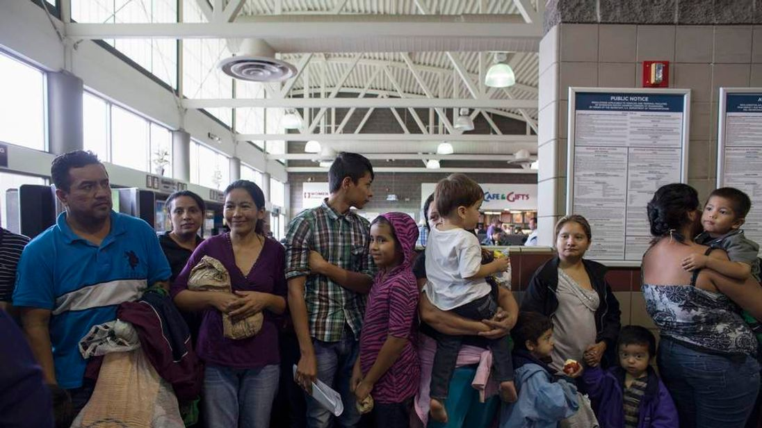 Migrants who just disembarked from a U.S. ICE bus wait for a Greyhound official to process their tickets to their next destination at a Greyhound bus station in Phoenix
