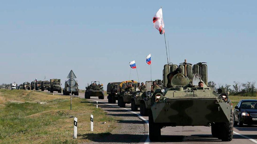 Russian military personnel ride atop APCs outside Kamensk-Shakhtinsky