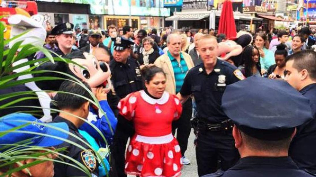 Police escort Sandra Mocha, as Minnie Mouse, out of Times Square