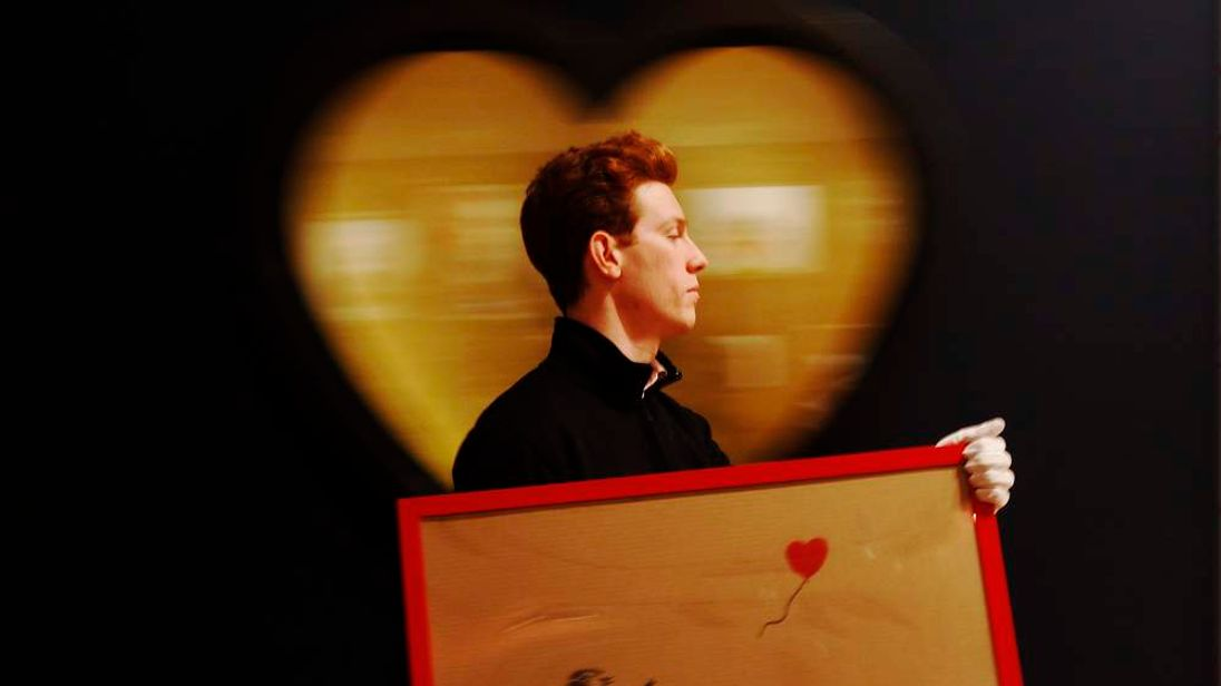 "An employee walks with artist Banksy's ""Girl and Balloon"" 2009 signed and inscribed For Mike, past artist  Ryan Callanan's (known as RYCA) ""Mega Heart"" 2011 at Bonhams auction house in London"