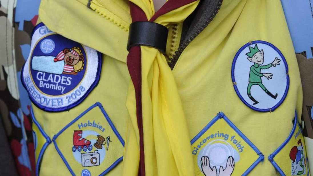 A Brownie displays some of the achievement badges on her uniform