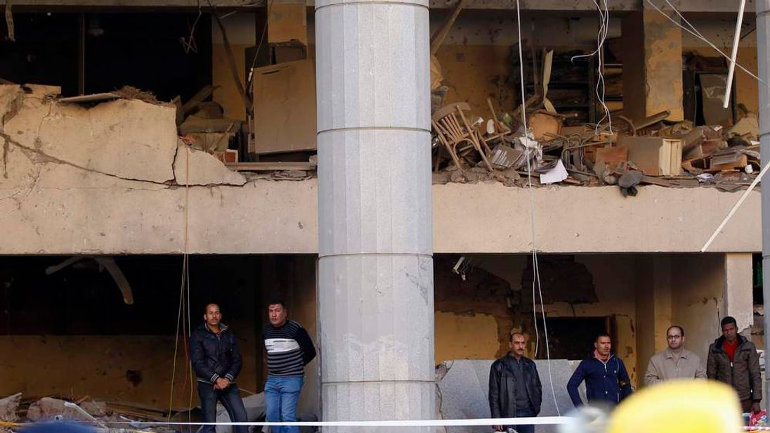Police officers inspect site of bomb attack in front damaged Cairo Security Directorate in Cairo