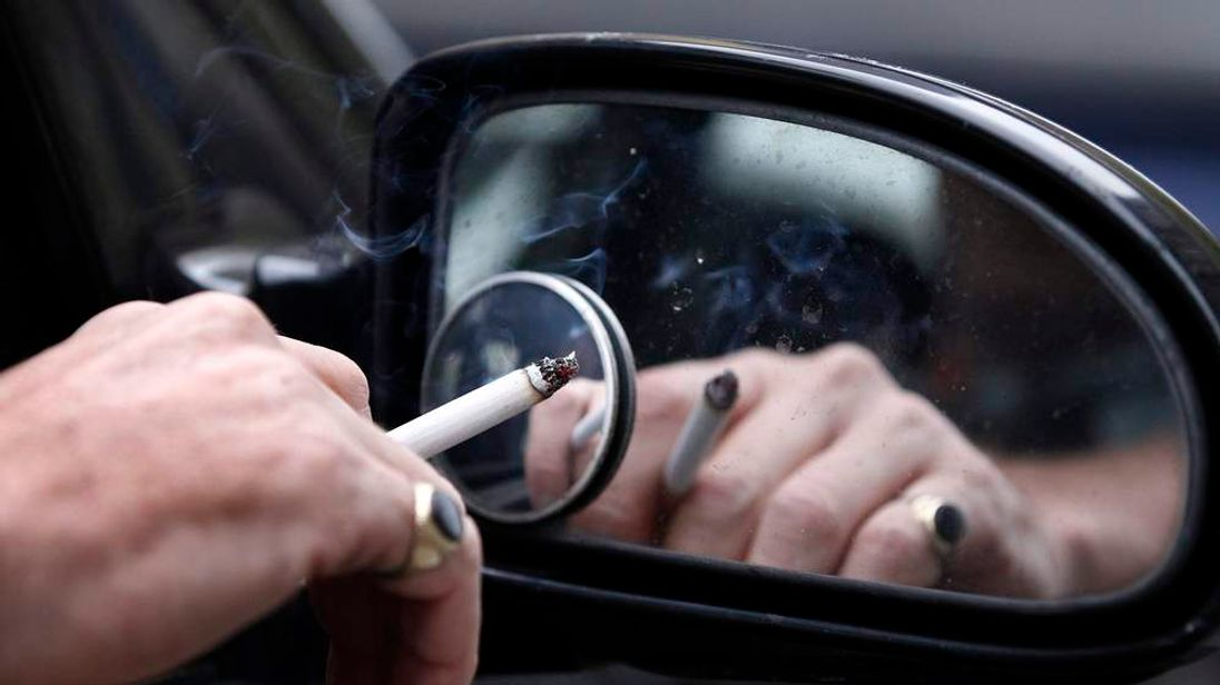 A man smokes a cigarette as he sits in his car in Liverpool
