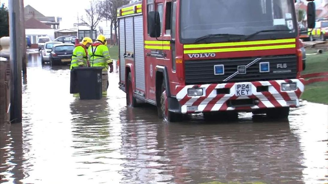 Firefighters wade through floodwater in Rhyl, north Wlaes