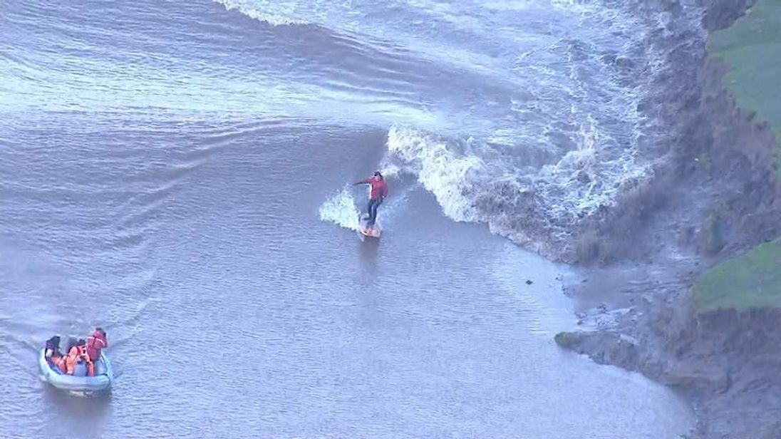 A Surfer Rides The Severn Bore Wave