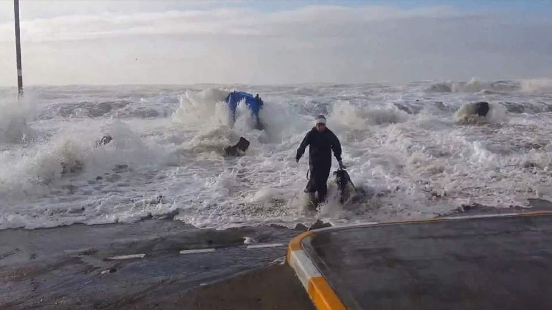 Dog walker is knocked over by rogue wave