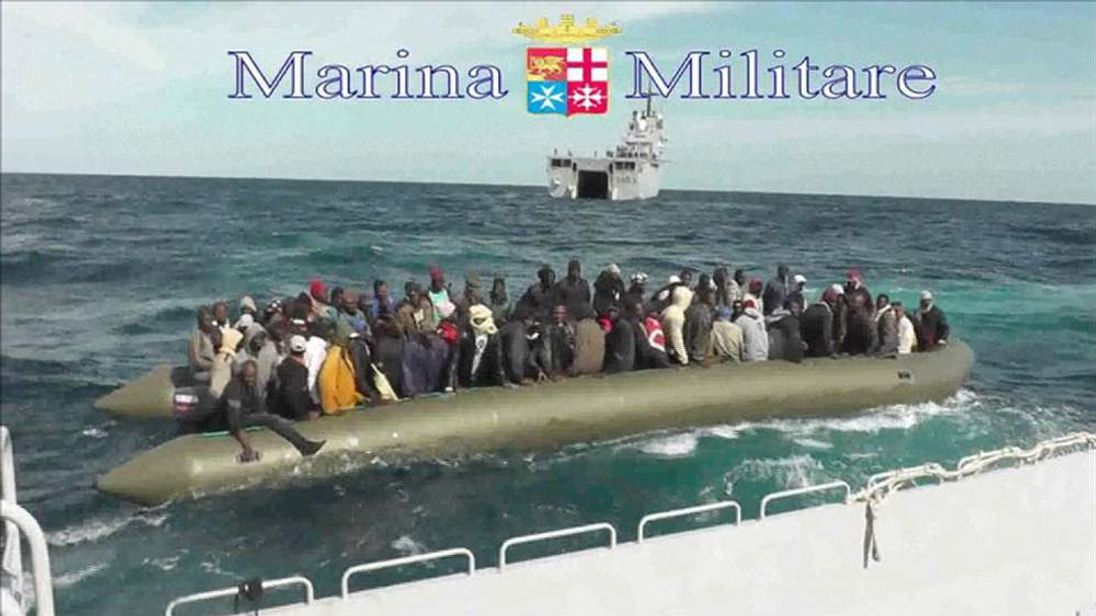 Italian authorities rescue migrants at sea in an inflatable dinghy