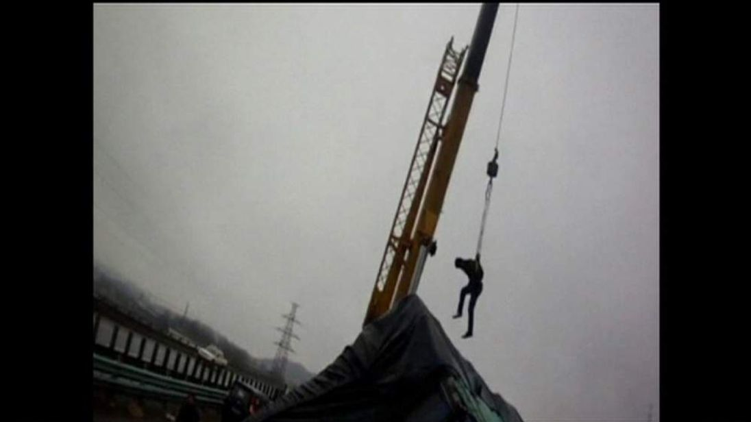 A man is rescued by crane after a truck crash in China