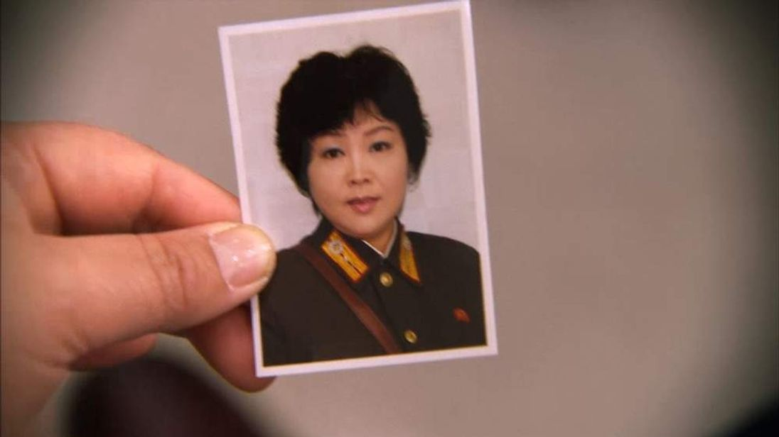 A North Korean defector holds a photograph of herself