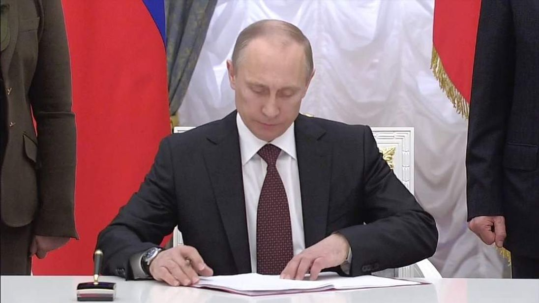 Russia's President Putin signs a bill confirming the annexation of Crimea.