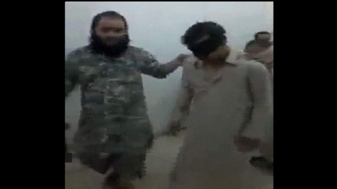 Isis fighter with captured Iraqi soldiers in Tikrit