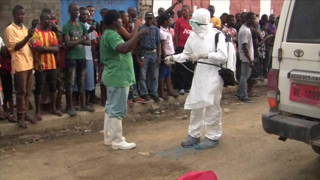 A man is disinfected to prevent the spread of ebola virus