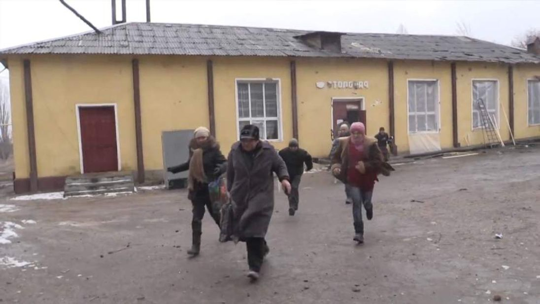 People flee a soup kitchen in Pervomaisk as it's hit by Grad rockets