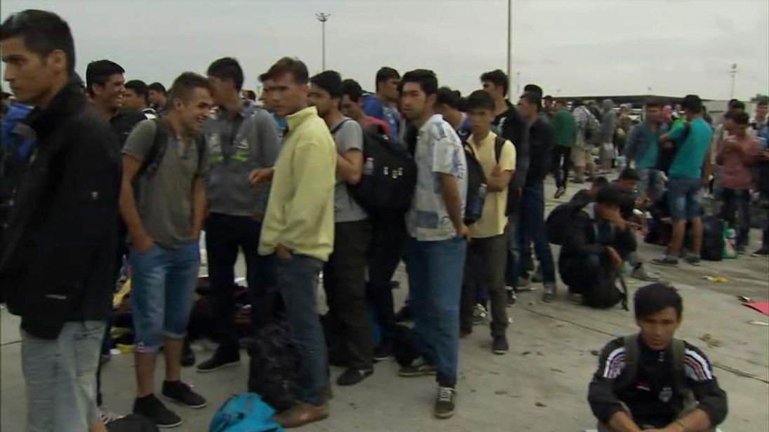 Migrants wait to be processed on the Austrian border