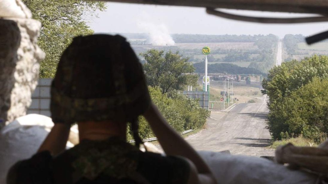 A Ukrainian soldier looks through binoculars at a checkpoint near Debaltseve, in the Donetsk region