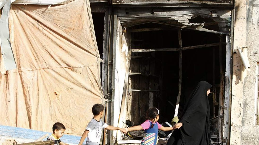 A family walks past the site of a car bomb attack at the neighbourhood of Tobchi in Baghdad