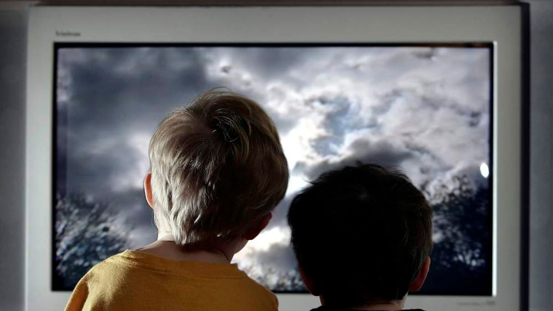 Two young children watch television at home in London.