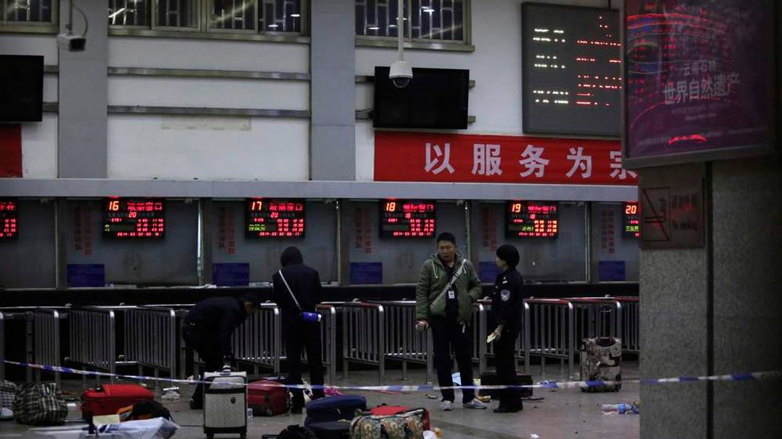 Police stand near luggages left at the ticket office after a group of armed men attacked people at Kunming railway station, Yunnan province