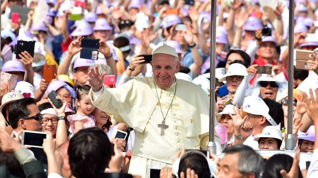 Catholic worshippers greet Pope Francis as he arrives in central Seoul