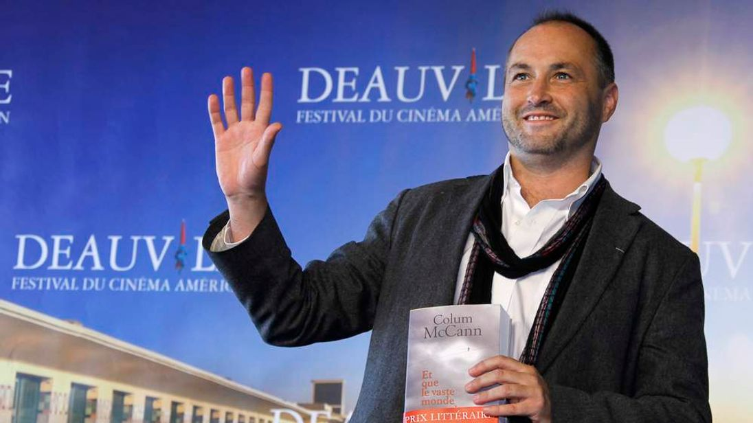 """Irish writer McCann poses with his book """"Let the Great World Spin"""", during a photocall after he won the Literary Award at the 35th Deauville American film festival in Deauville"""