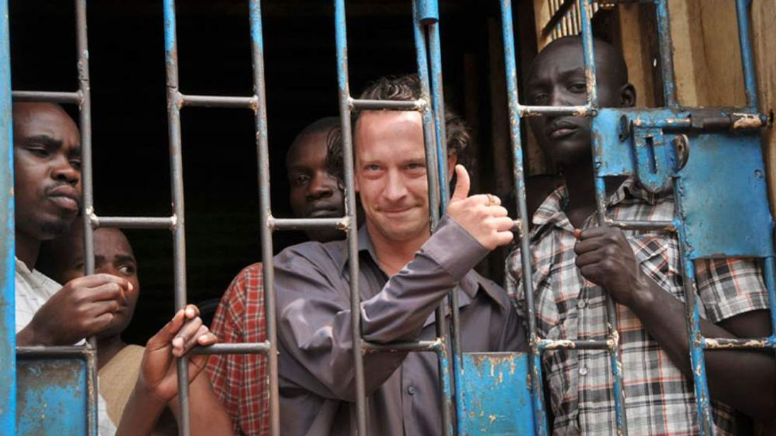"""David Cecil, the British producer of the play """"The River and the Mountain"""" concerning the condition of Uganda's gays, stands in a court cell in the capital Kampala, Uganda Thursday, Sept. 13, 2012."""