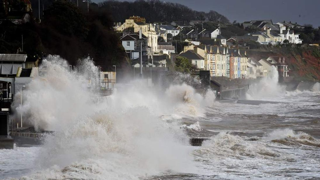 Waves break across the length of the sea wall in Dawlish