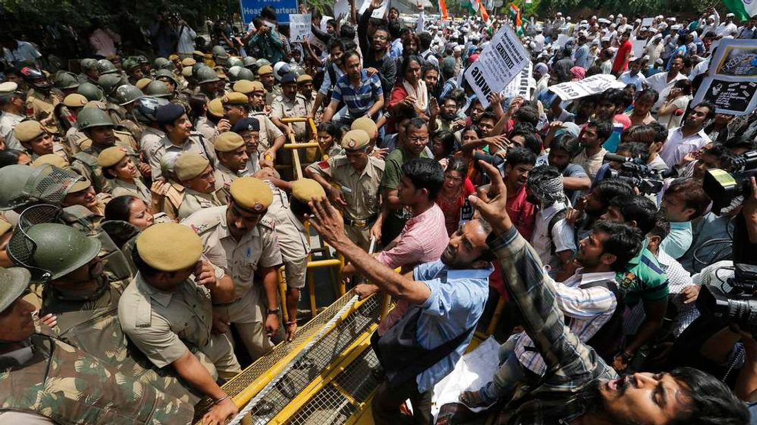 Demonstrators shout as they try to cross a police barricade during a protest outside police headquarters in New Delhi